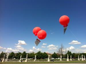 tre palloni giganti rossi ad elio con un banner pubblicitario appeso sotto