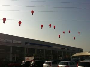 11 Mongolfiere promozionali rosse sospese a 10 metri di altezza sopra il tetto di una concessionaria