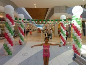 4 colonne tricolore di palloncini e al centro bambina vestita di rosa
